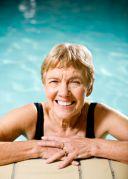 Eine glückliche Frau am Schwimmbeckenrand